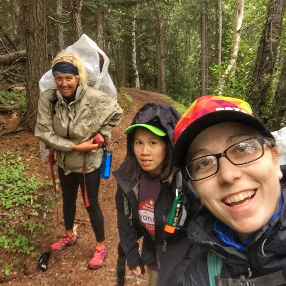A group of three female hikers, with rain gear, hiking in a forest.