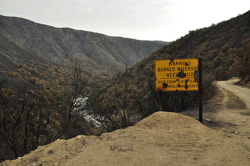 A photo of a warning sign and a valley showing the after effects wildfires