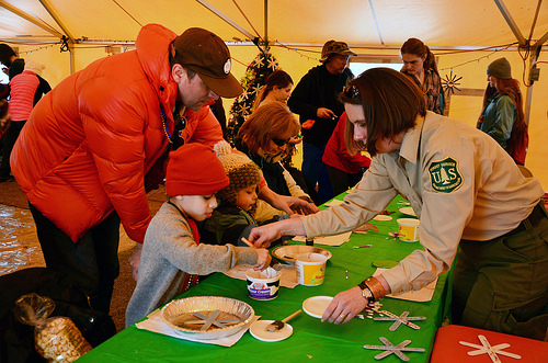 A photo of Forest Service employee Cheyenne Warner helps children make ornaments