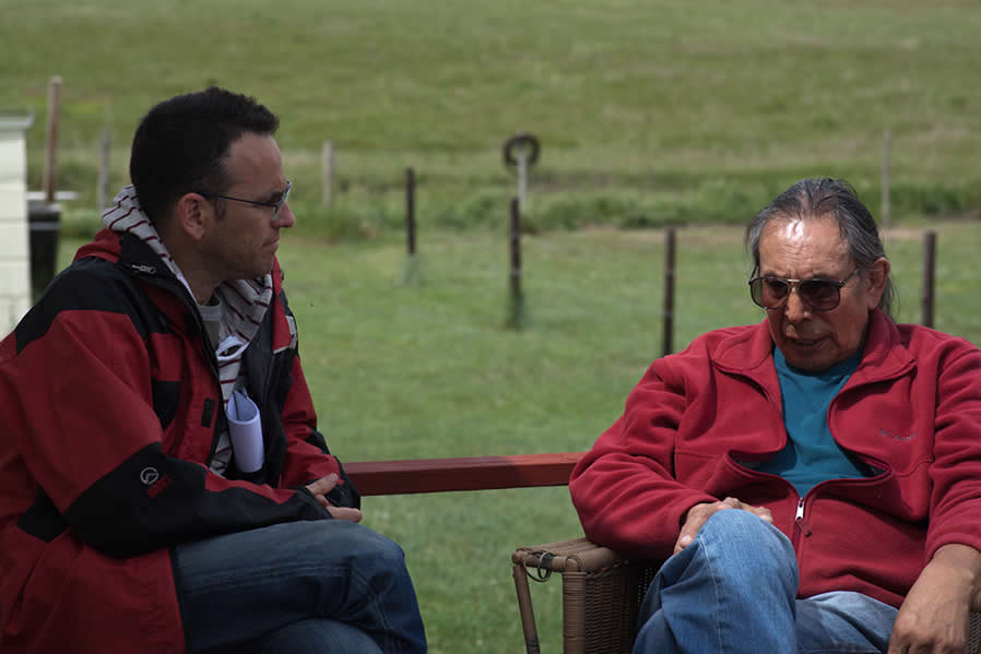 Documentary filmmaker Jonathan Skurnik listens to Walter Littlemoon at Walter's house in Wounded Knee, South  Dakota.