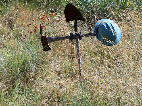 A cross made of a hard hat, shovel and Pulaski used by wildland firefighters stands at the Wildland Firefighters Monument in Boise, Idaho.