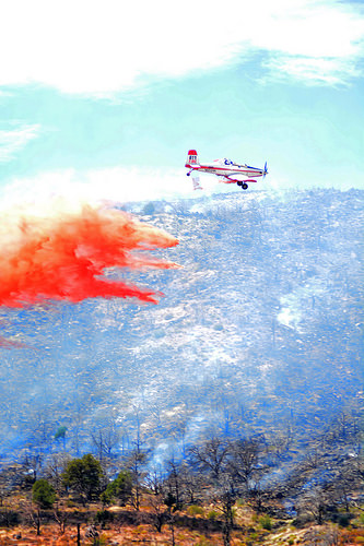 A Single Engine Airtanker, or SEAT, flies over a wildland fire dropping retardant.