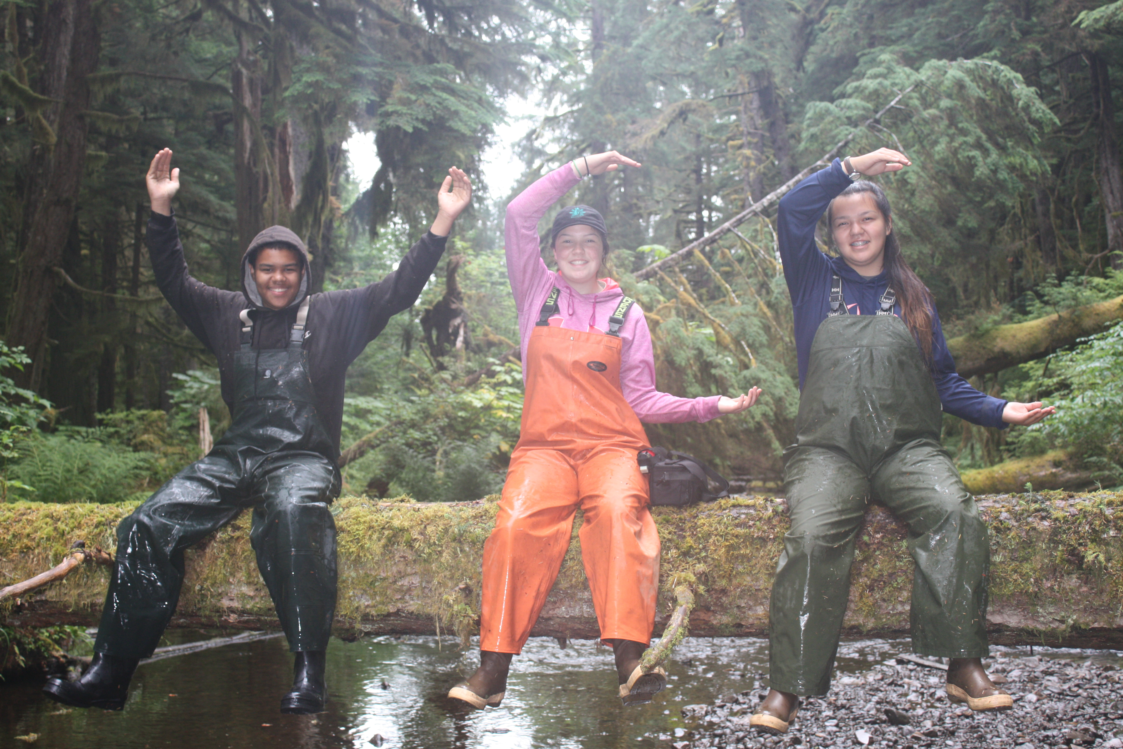 Photo: Group of three Angoon Youth Conservation Corps members pose for the camera making the YCC symbol in the YMCA style