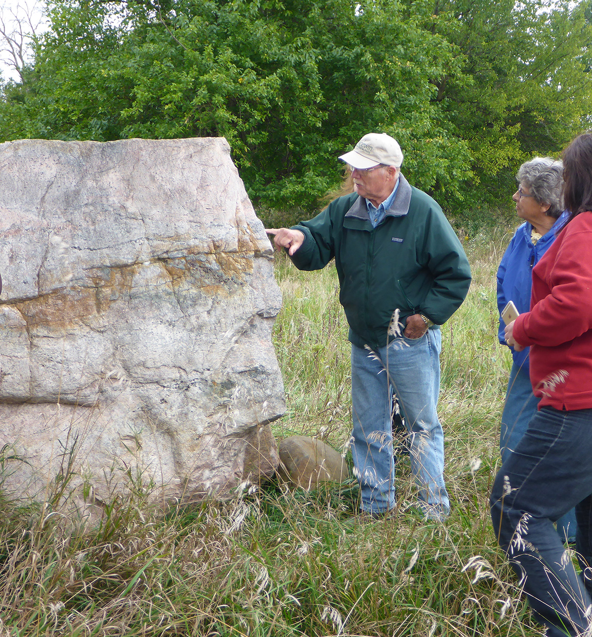 Photo: man stands in tall prairie grass and points to features of huge boulder. Boulder is as tall as he is. Two people are watching.