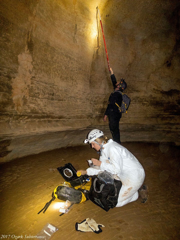 Doty & a colleague in a cave, using equipment to collect air samples.