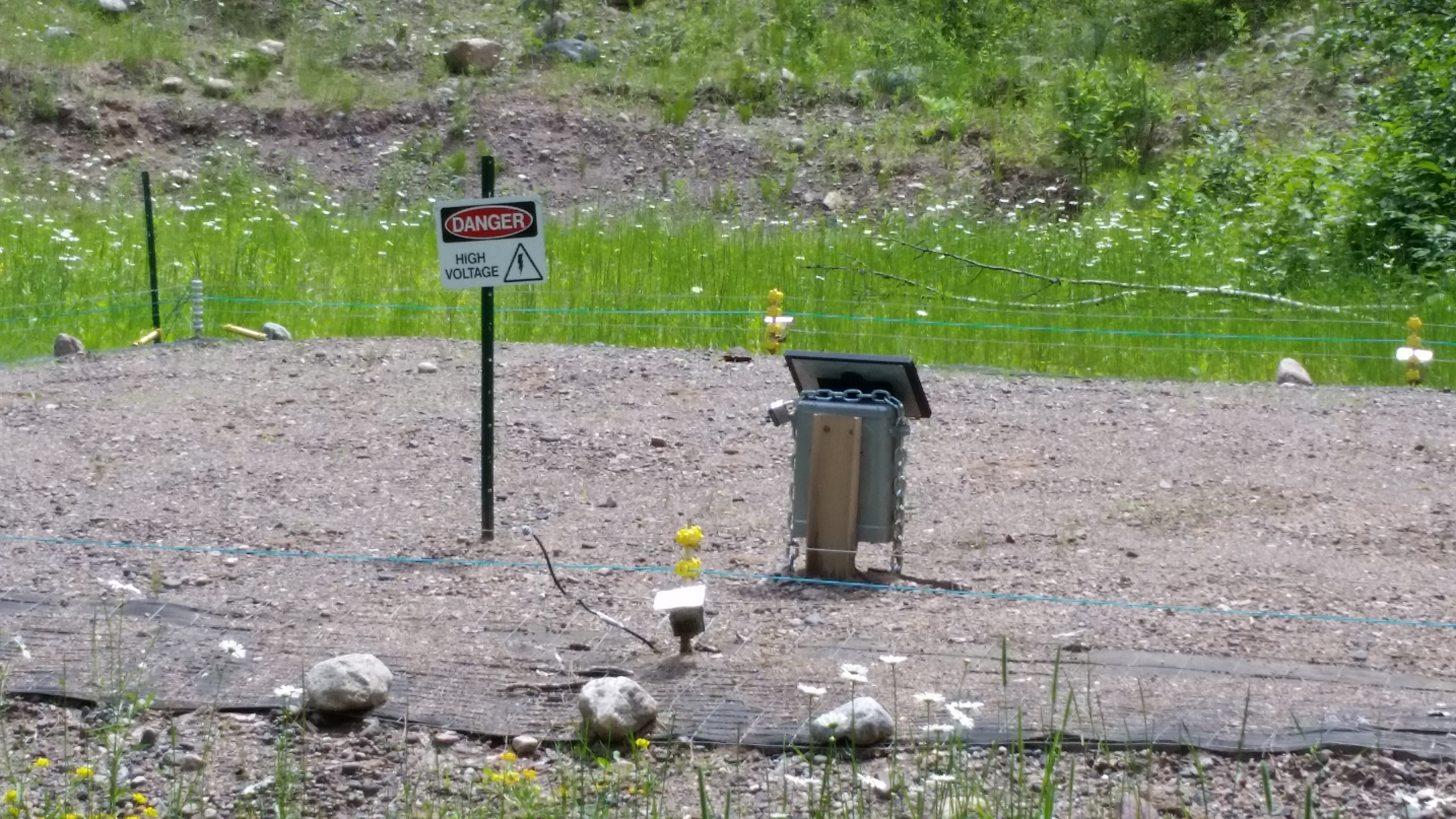 A picture showing a Danger, High Voltage sign, protecting area meant to accommodate adult turtles or further protect hatchlings.
