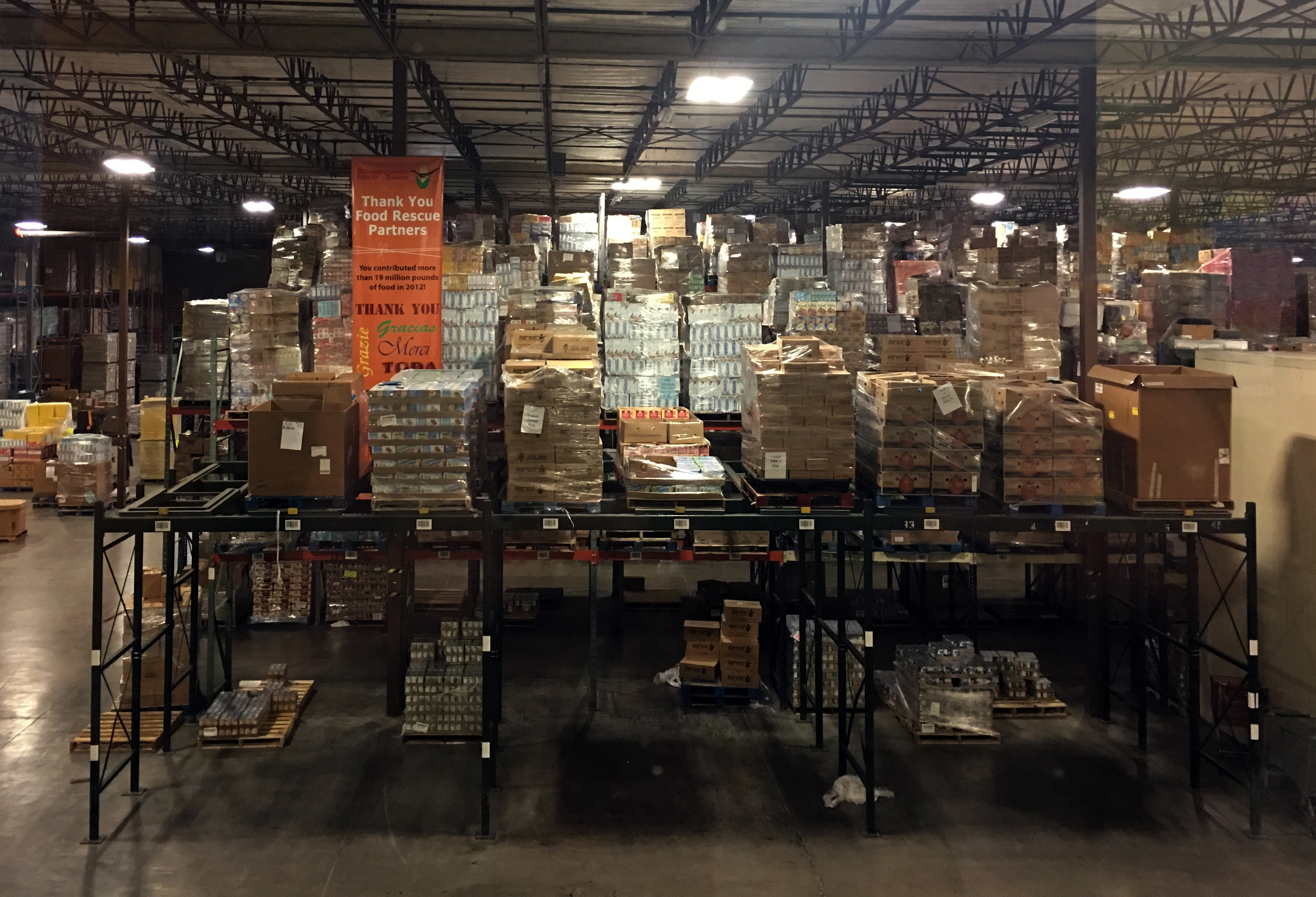 Piles of food and commodities in a large warehouse.