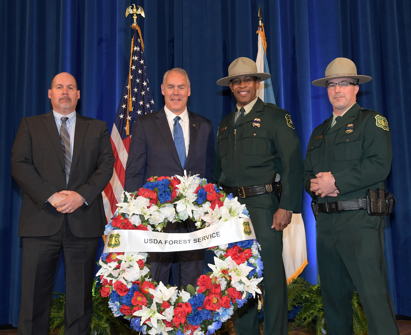 Photo: Forest Service law enforcement personnel stand with Interior Secretary Ryan Zinke and Forest Service memorial wreath.