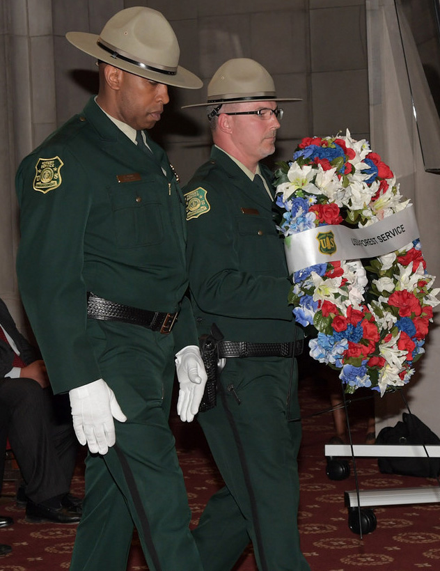 Photo: Tracy Perry & Tony McGallicher carry a wreath at memorial ceremony.