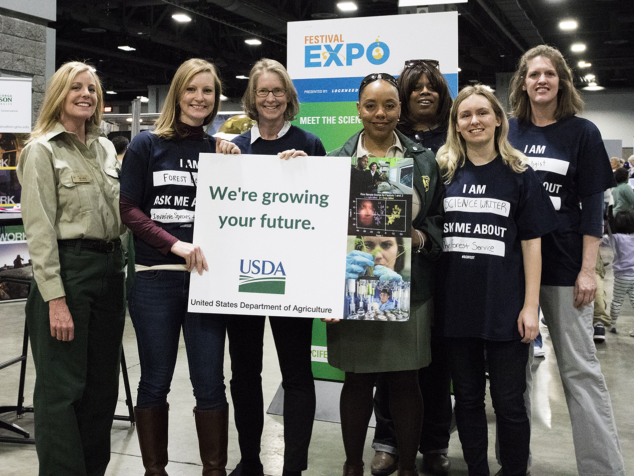 "Photo: Forest Service employees hold a sign saying ""We're growing your future"" at the 2018 STEM expo."