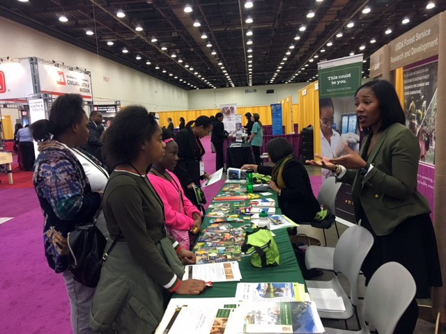 Beattra Wilson staffs a table at a career fair.
