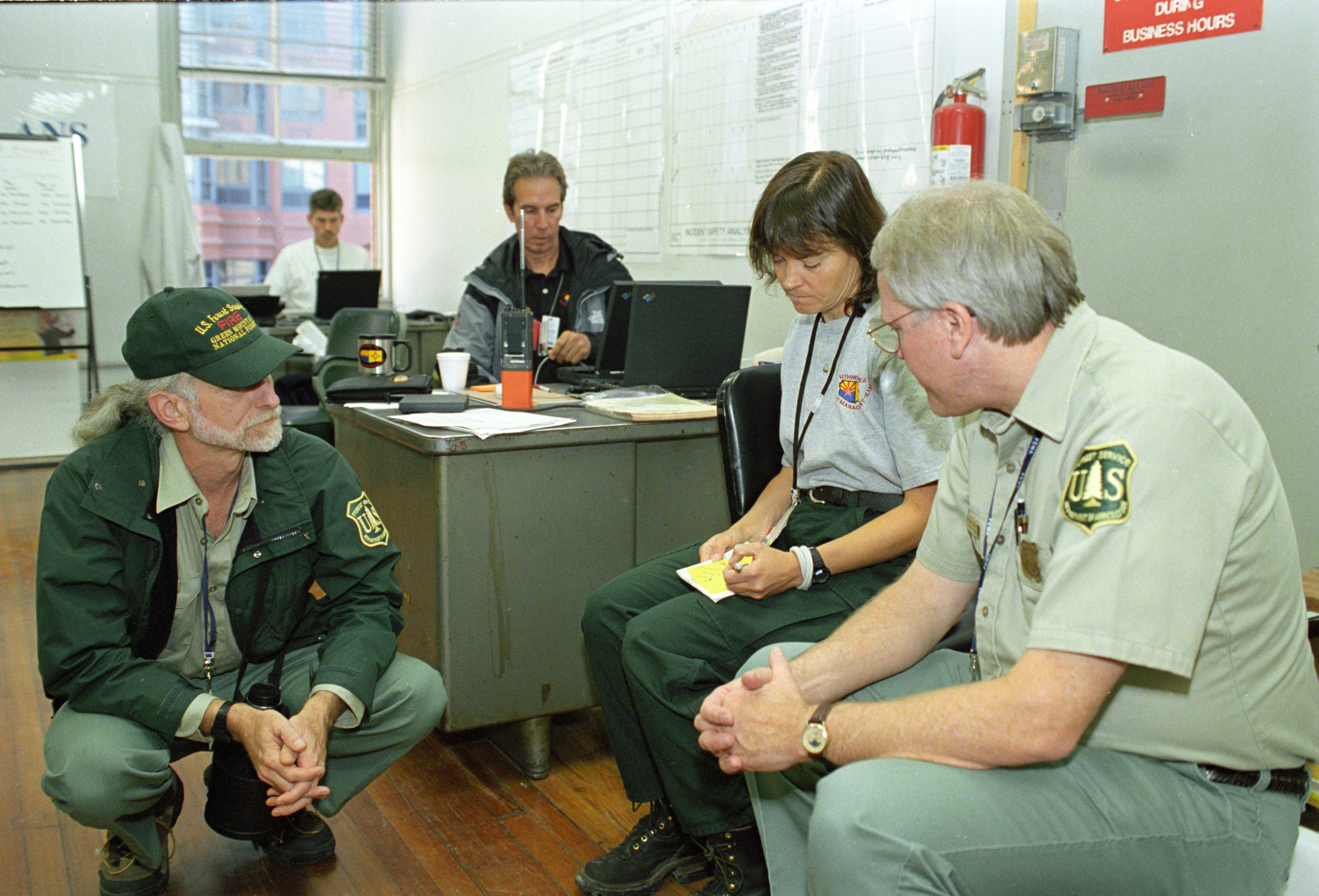 Forest Service and incident management employees in a room discussing things.