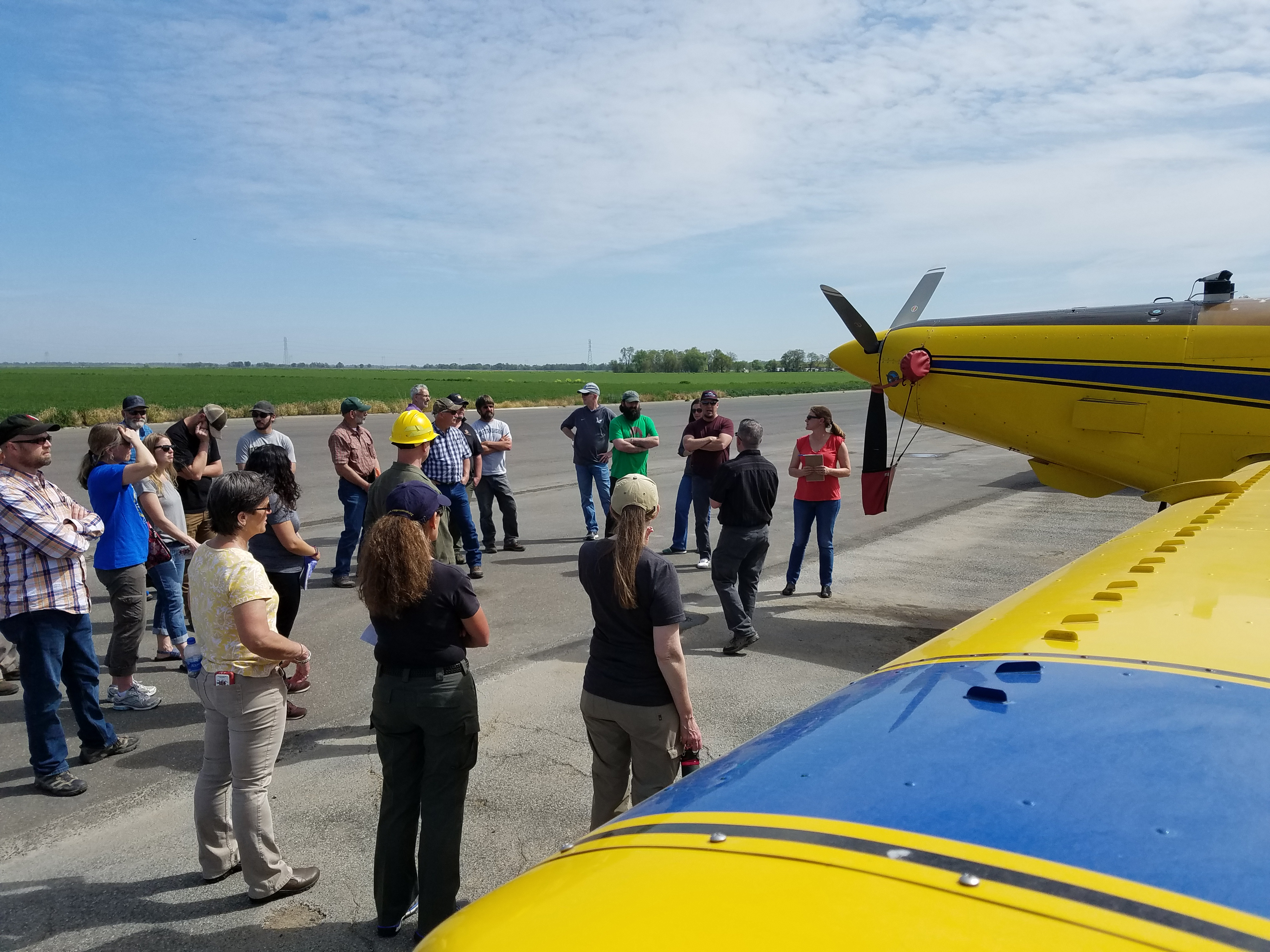 Photo: A group of people standing on tarmac around air tractor listen to Serena discuss air safety.