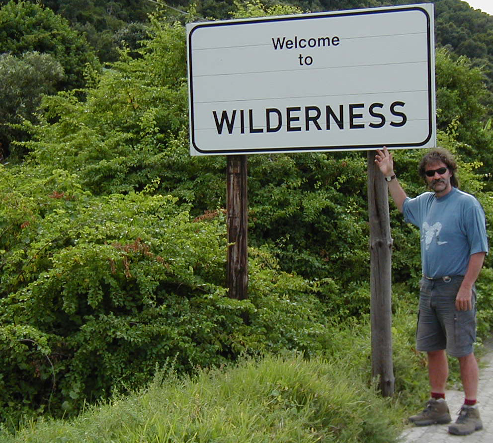Alan Watson standing next to a Welcome to Wilderness sign.