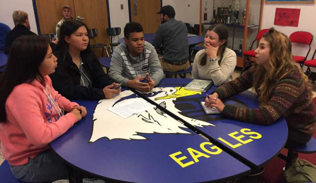 A photo of five Angoon youth sitting around a table talking about conservation