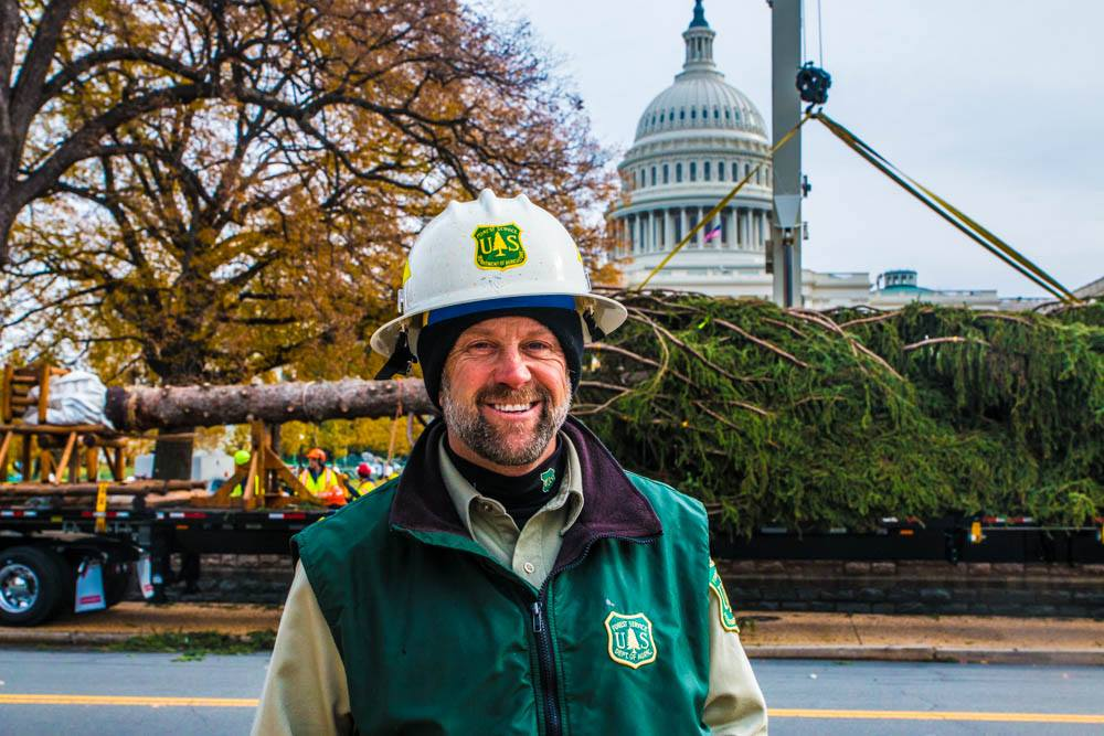 A photo of Chris Niccoli standing in front of 2016's U.S. Capitol Christmas tree from Idaho to Washington, D.C.
