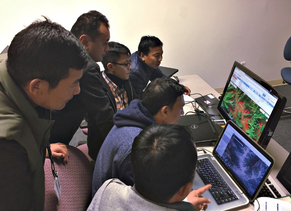 Photo: Bhutanese foresters cluster around two laptops. One screen shows a map, the other shows a picture of lush forest.