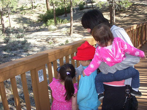 A family playing with the Discovery Agents app at Chilao Visitor Center in the Angeles National Forest, uses a conveniently located QR Code. (Forest Service photo)