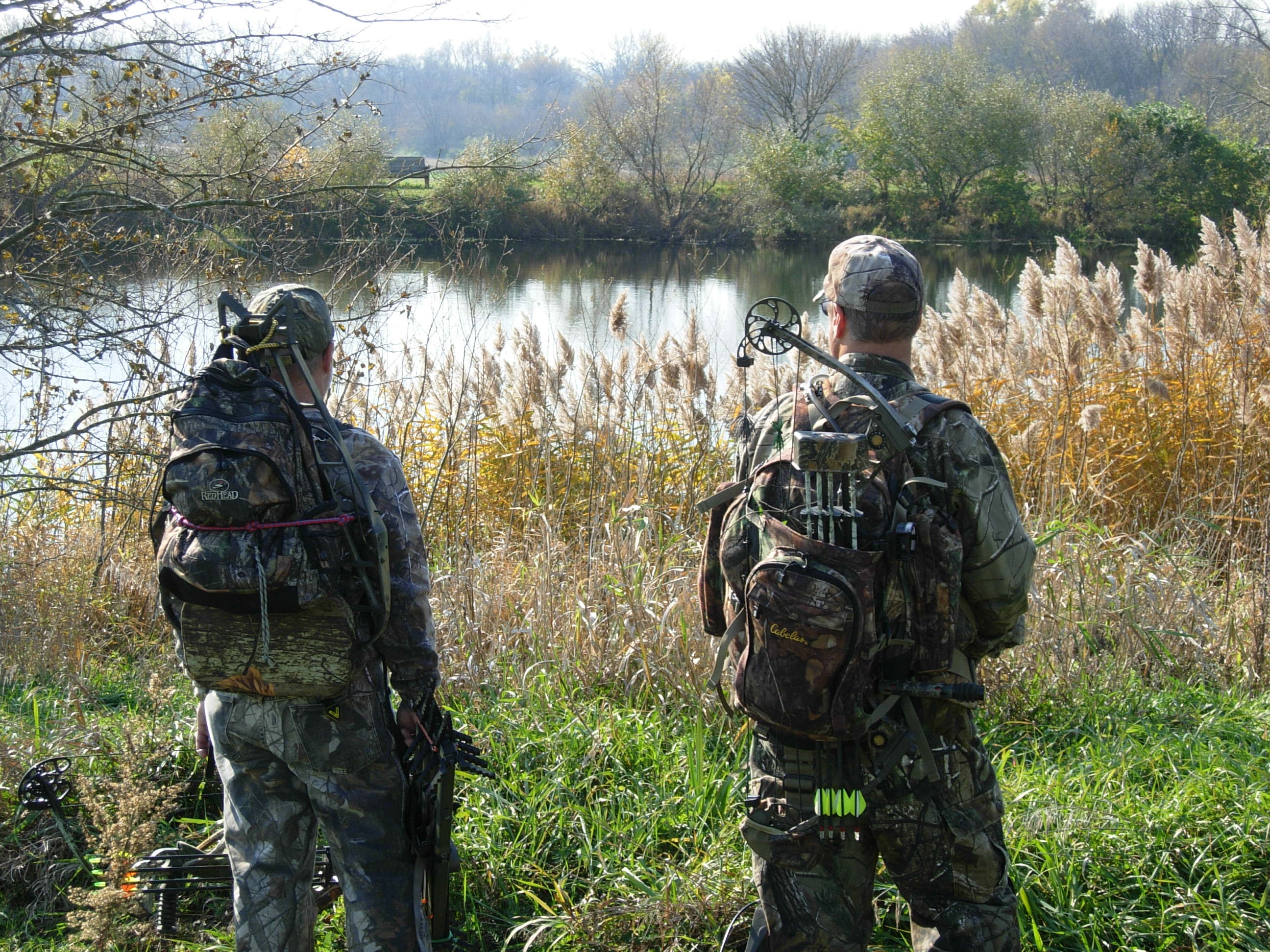 A picture of two bow hunters all in camouflage looking out over a river grassy river bank.