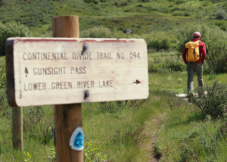 A picture of a person hiking on the CDT with a wooden trail sign in the foreground.