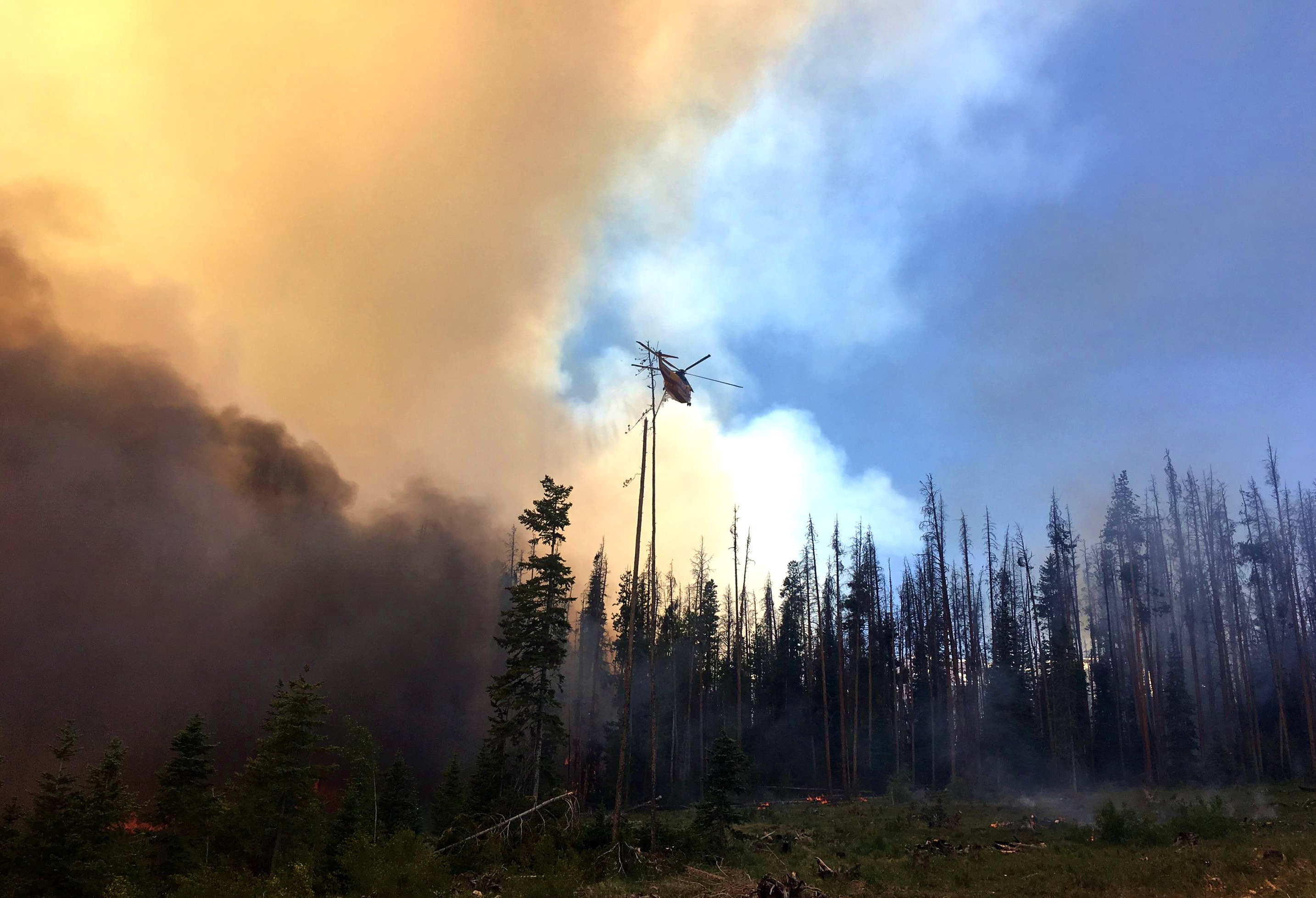 Photo: Smoke rises from forest as helicopter drops water.