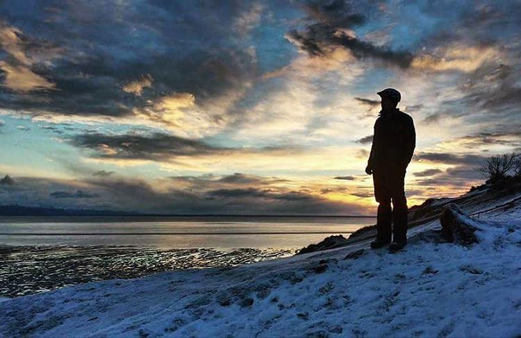 A photo of a man standing by the shore looking at the ocean.