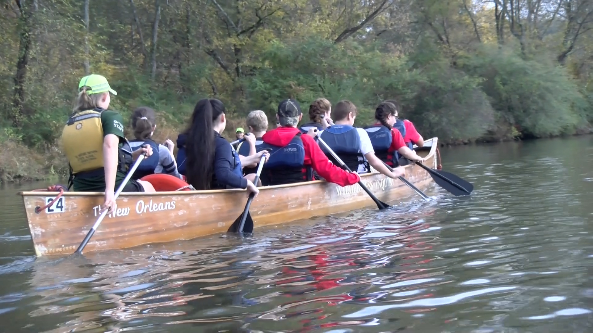 Students rowing on a canoe down a river
