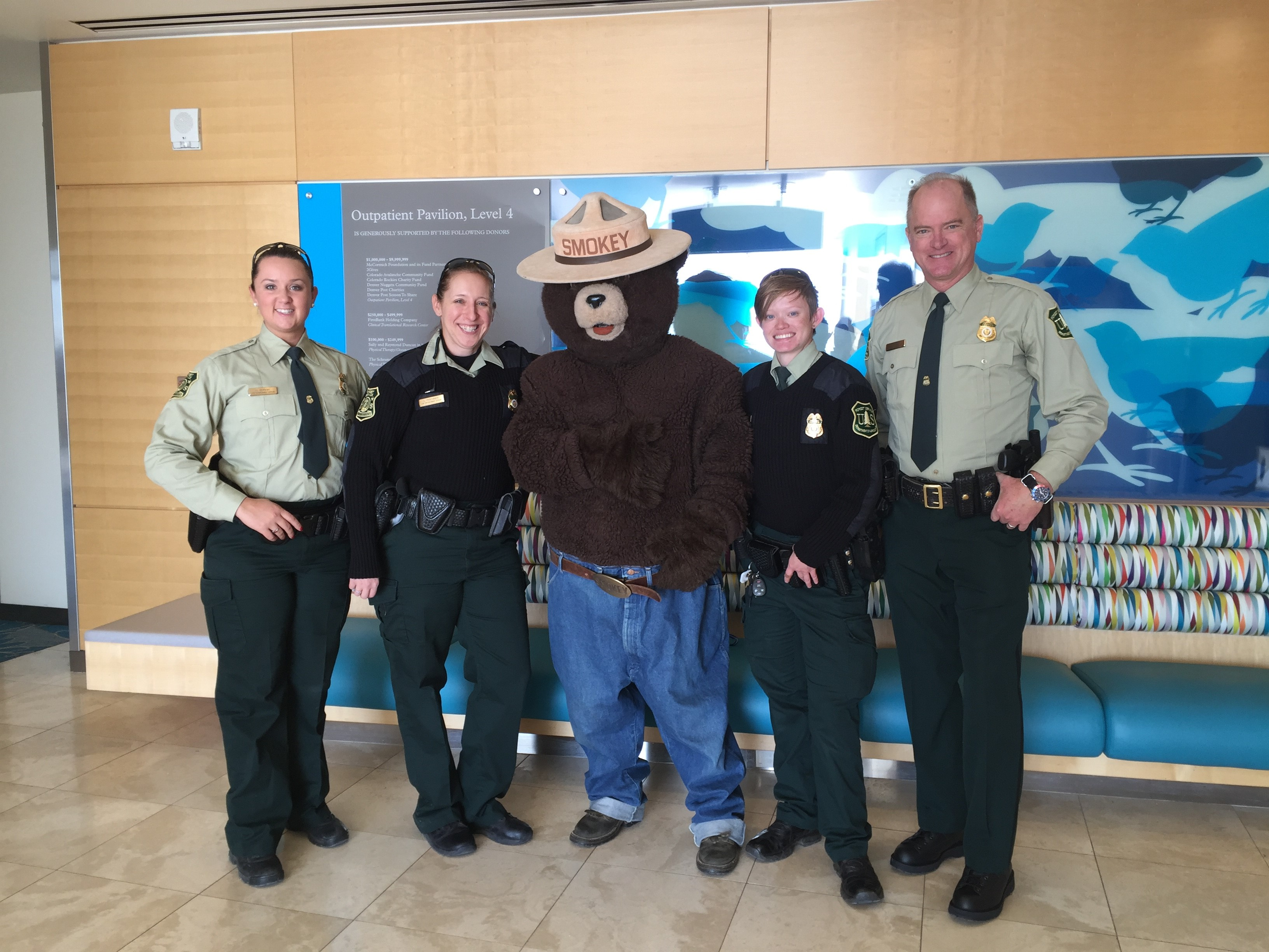 Hannah Nadeau and colleagues pose with Smokey Bear at a charitable event.