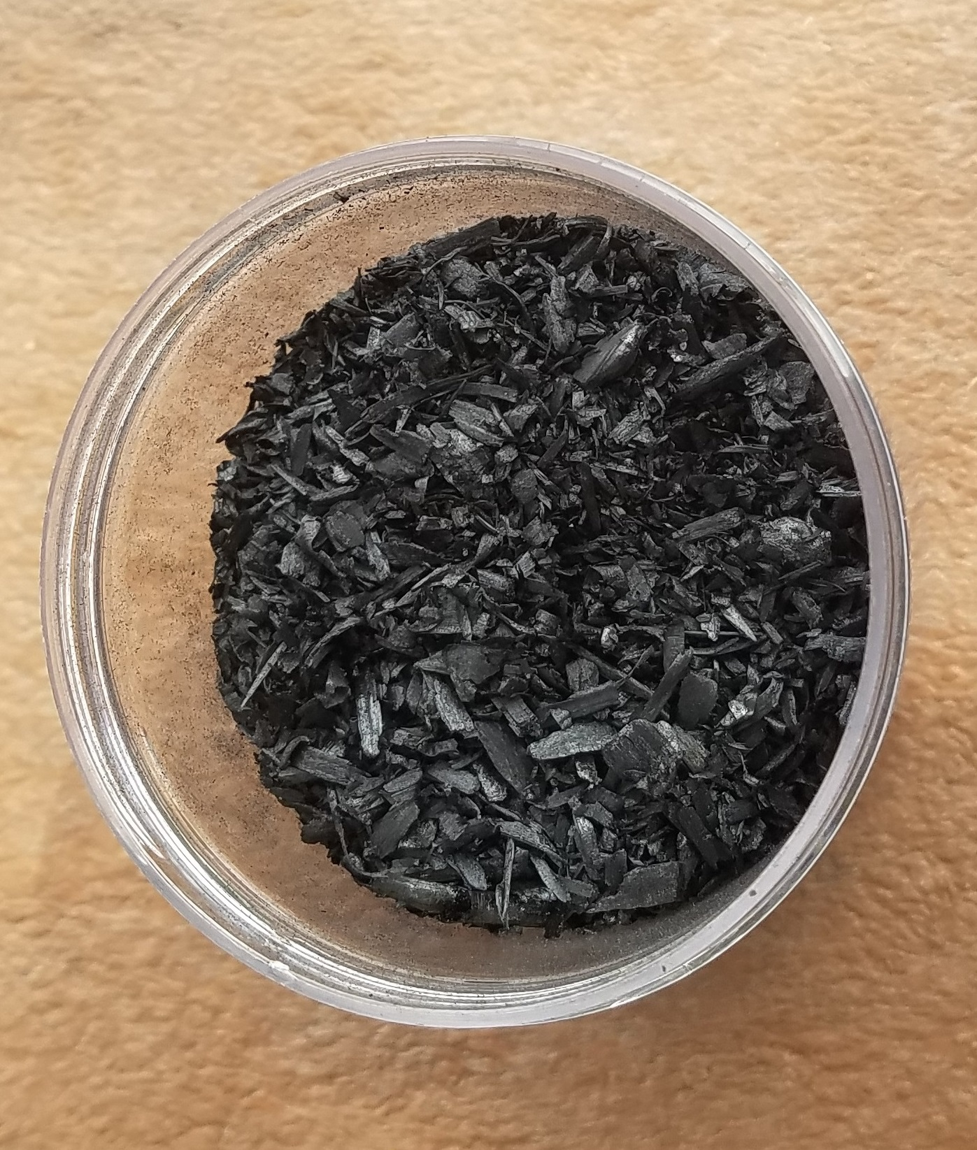 A small container with coarse biochar inside; small black colored pieces.