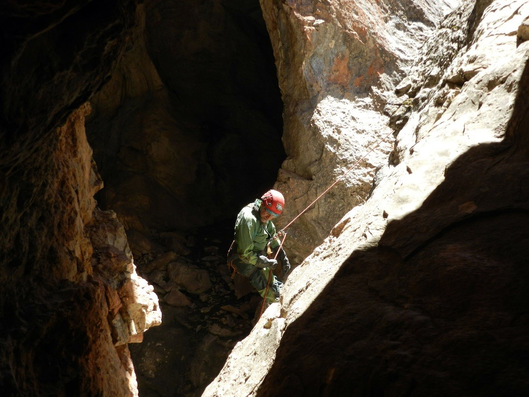 Photo: Person in safety harness and helmet rappels down into a cave.