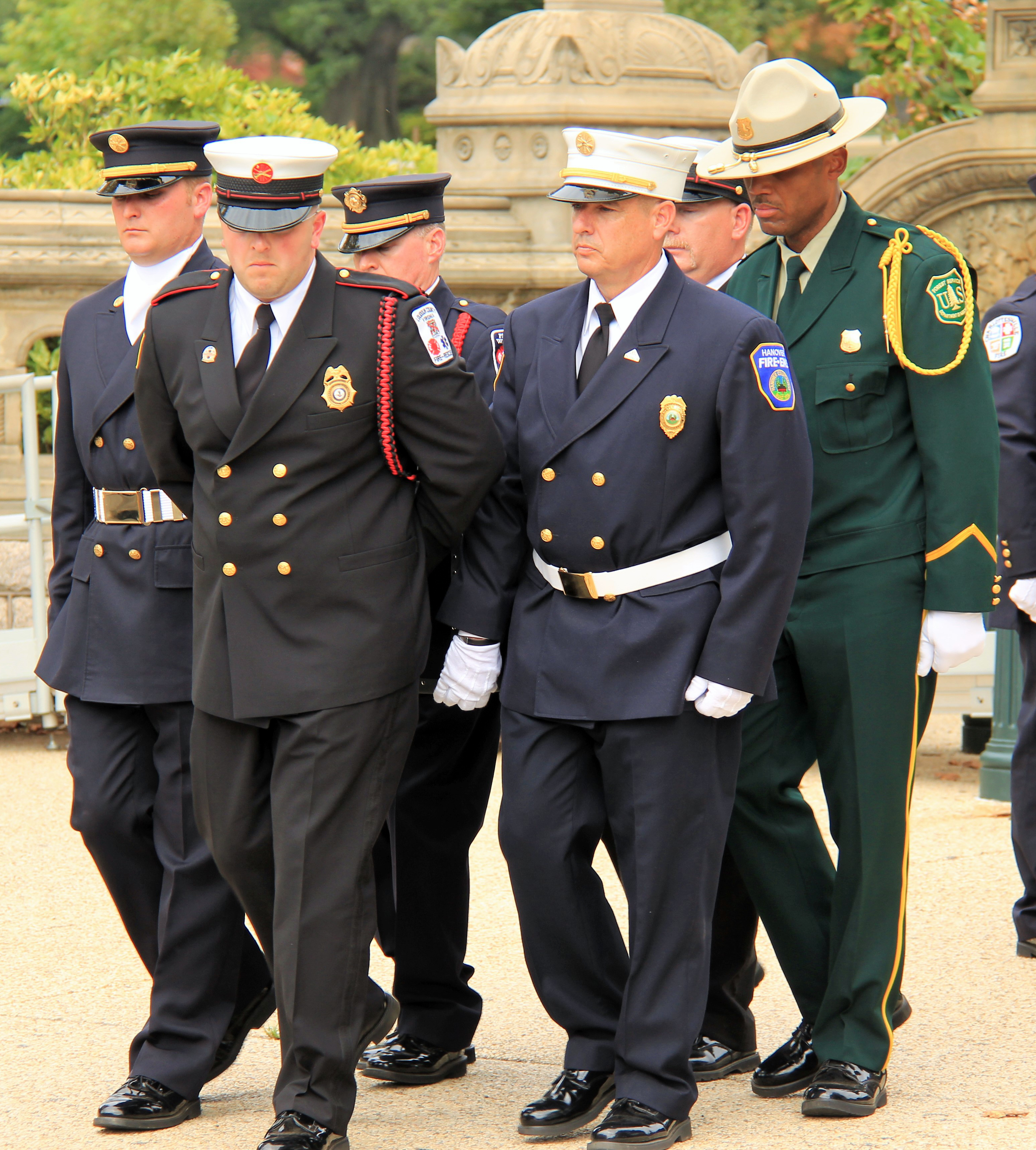 Men in uniforms of various agencies standing outside at the National Fallen Firefighter Foundation Memorial.