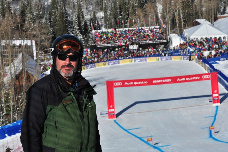 A picture in Don Dressler in skiing attire and helmet with the World Cup finish line behind him.
