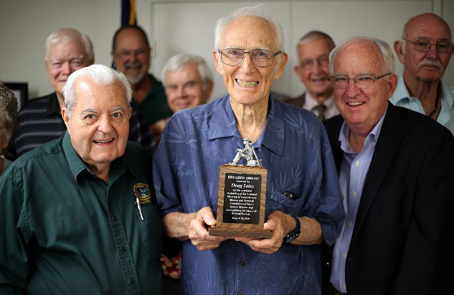 Doug Leisz holding his award. He is flanked by Tom Thompson and Al West.