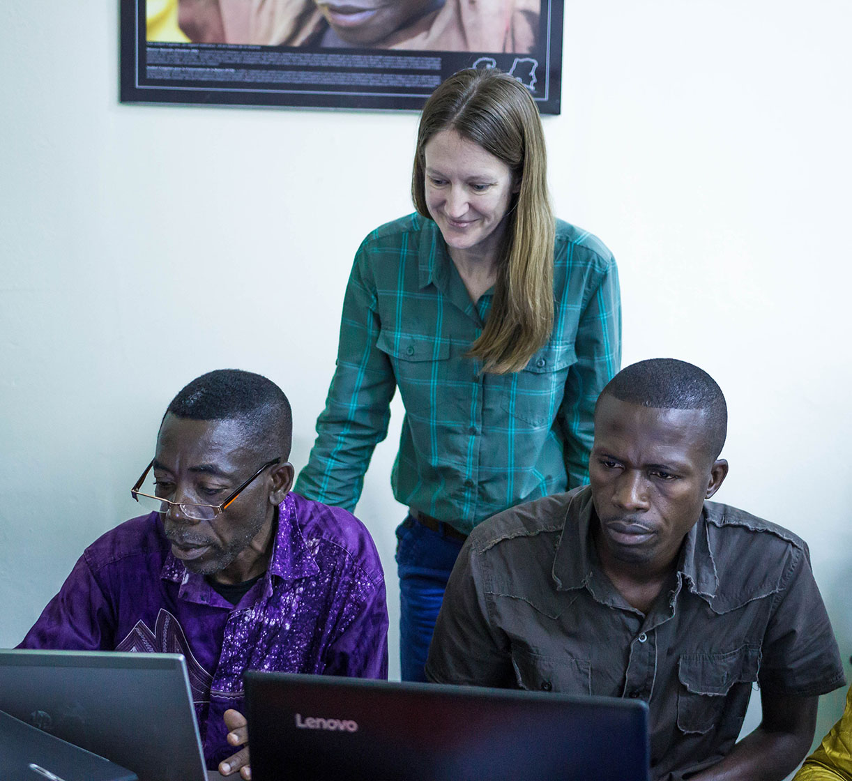 Photo: A woman stands behind two men who are working on computers.