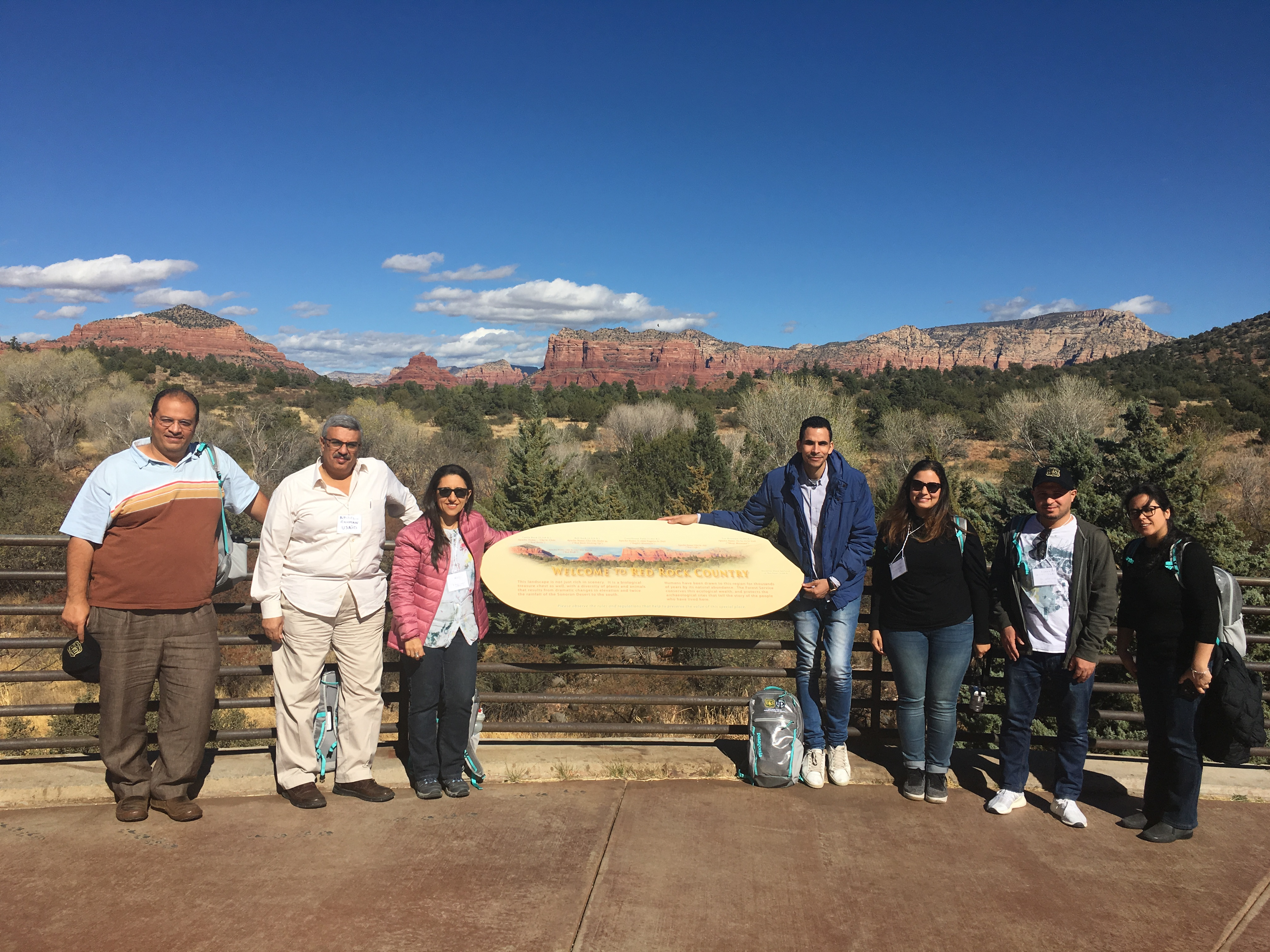 Photo: A group of people poses on either side of an interpretive sign. A mountain range is seen in the distance.