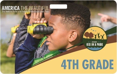 the cover of 2018 every kid in a park pass, a young fourth grader holding a pair of binoculars.