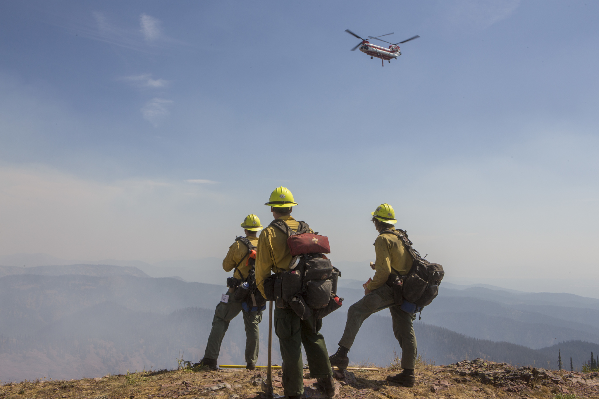 Firefighters watching helicopter on wildfire incident
