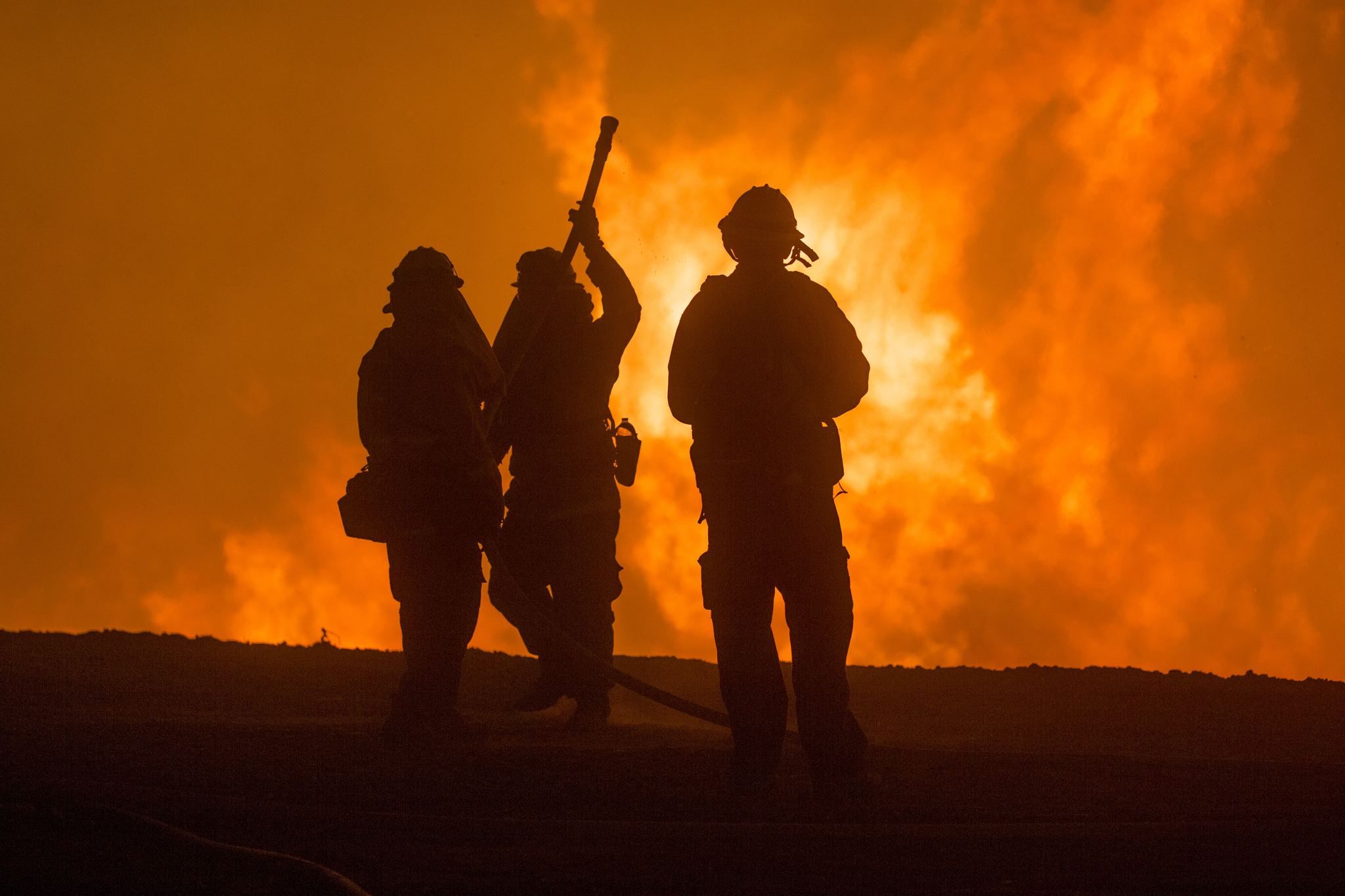 Three firefighters stand in front of a blaze