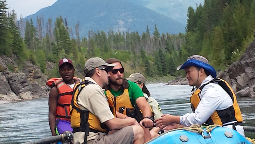 A photo of Florence Mdodi, Chris Prew, Christian Wyatt, Colter Pence, and Huang He on a raft with Flathead National Forest River Managers on the Middle Fork of the Flathead River