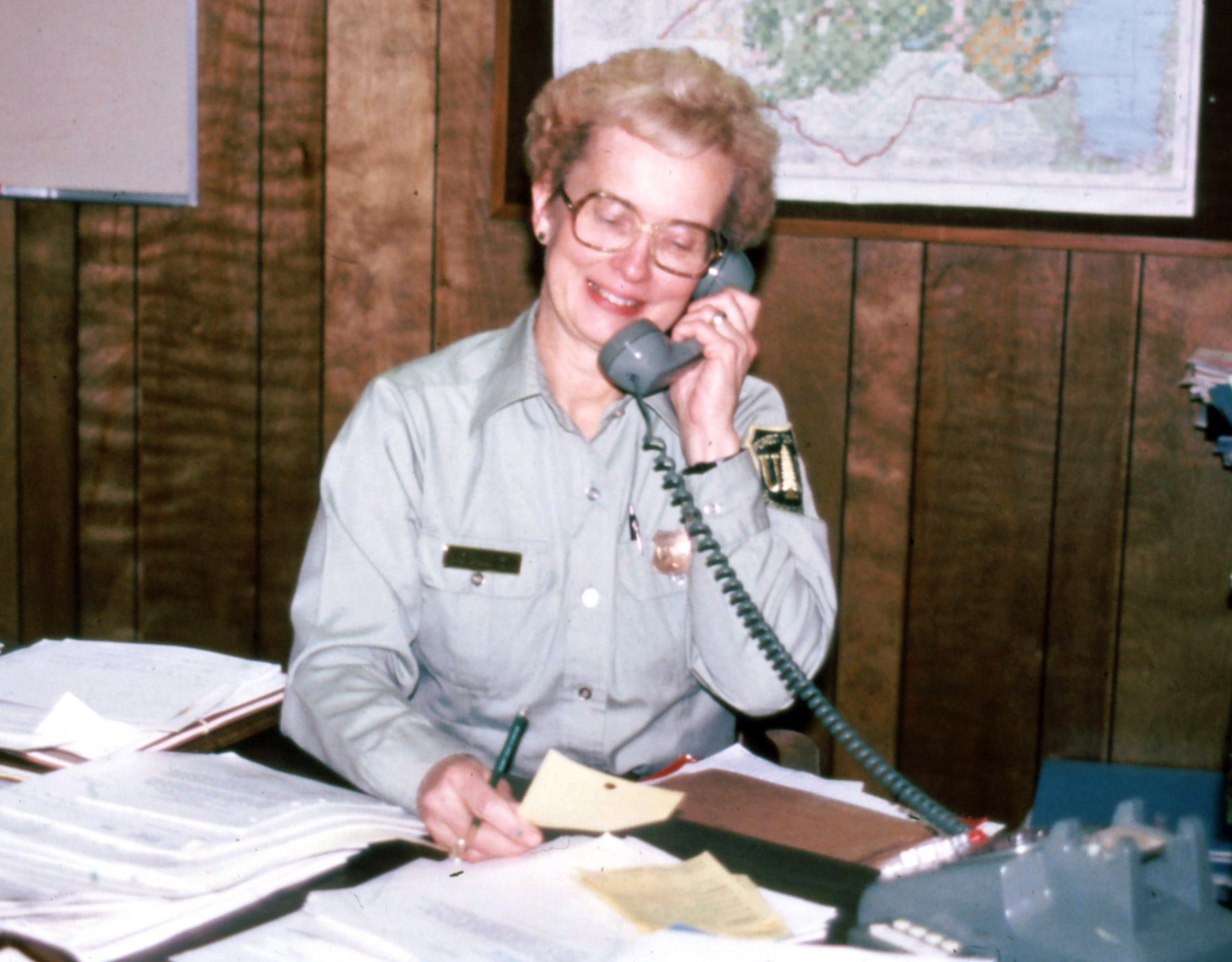 Geri Bergen, behind her desk, which is covered with files.
