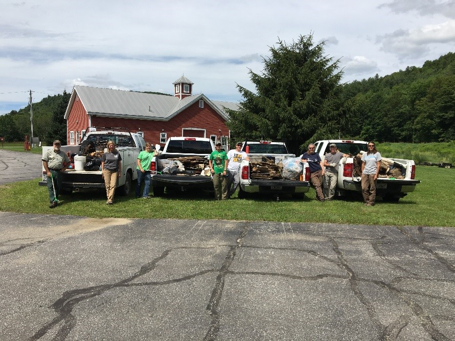 Photo: four pick-up trucks with their beds full of trash bags collected from Green Mountain National Forest