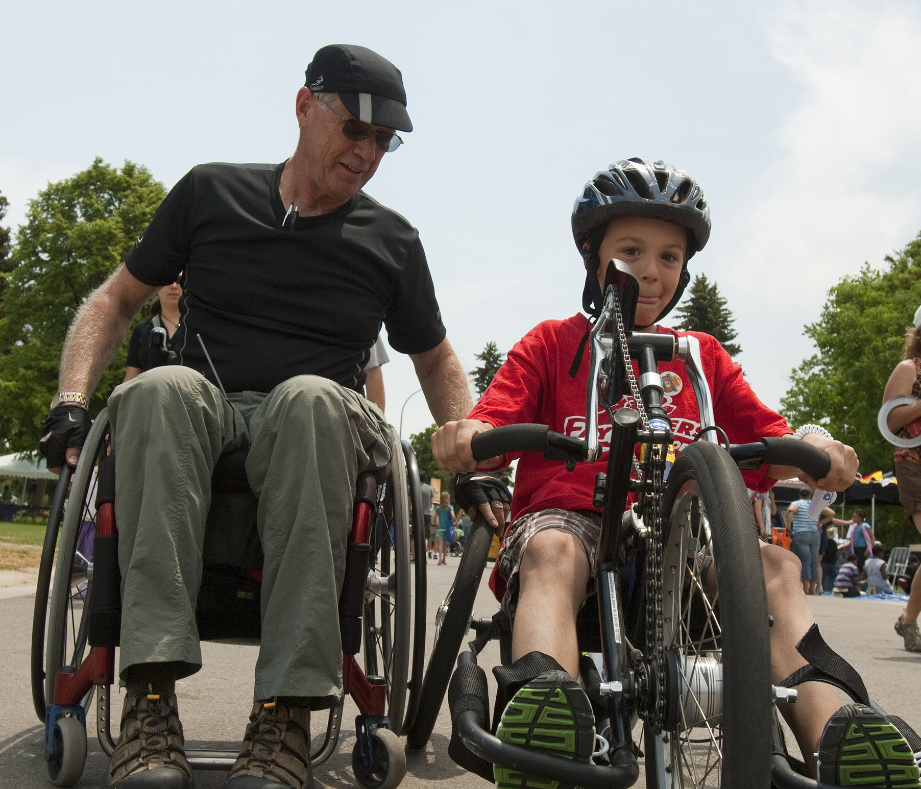Photo: Man in wheelchair teaches a young boy how to hand-pedal a bike designed for people with disabilities.