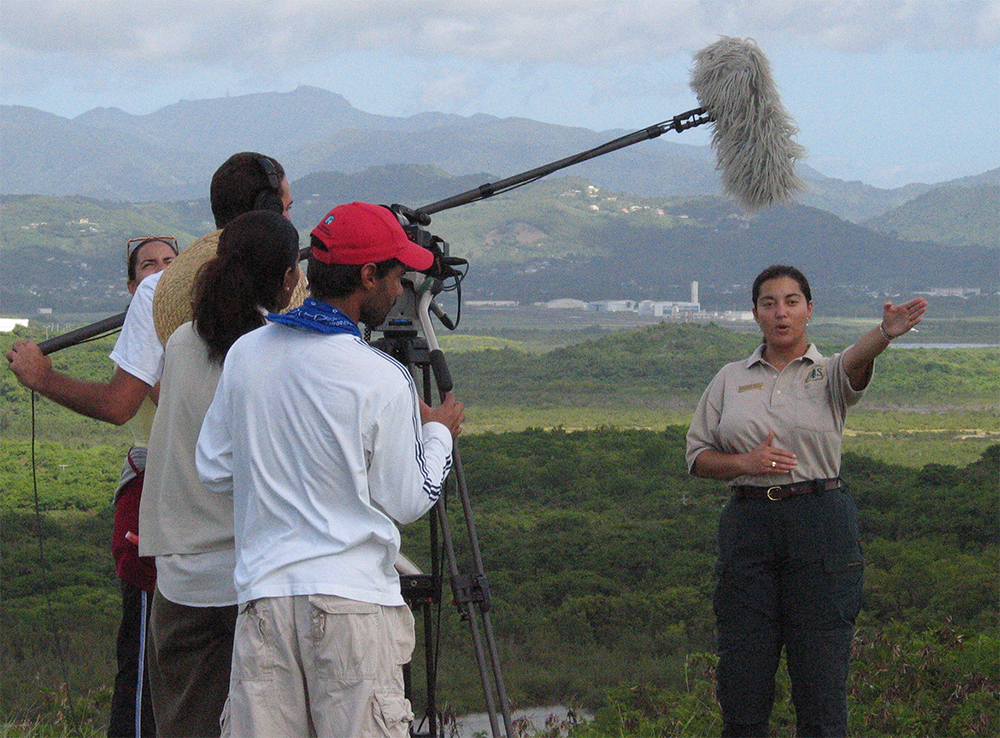 A photo of Grizelle with the filming crew of the a local television program