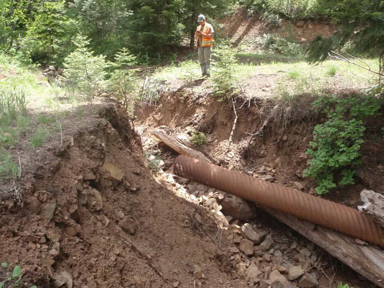 A crewmember examines a collapsed stream crossing in Idaho as part of GRAIP's forest road inventorying process
