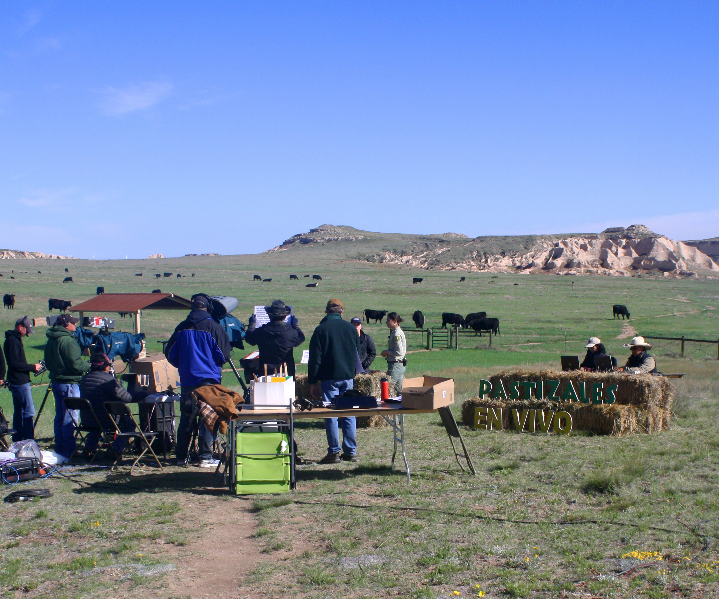 Photo: Cast and crew stand on the set of GrasslandsLIVE with grazing cattle and butte formations in the background.