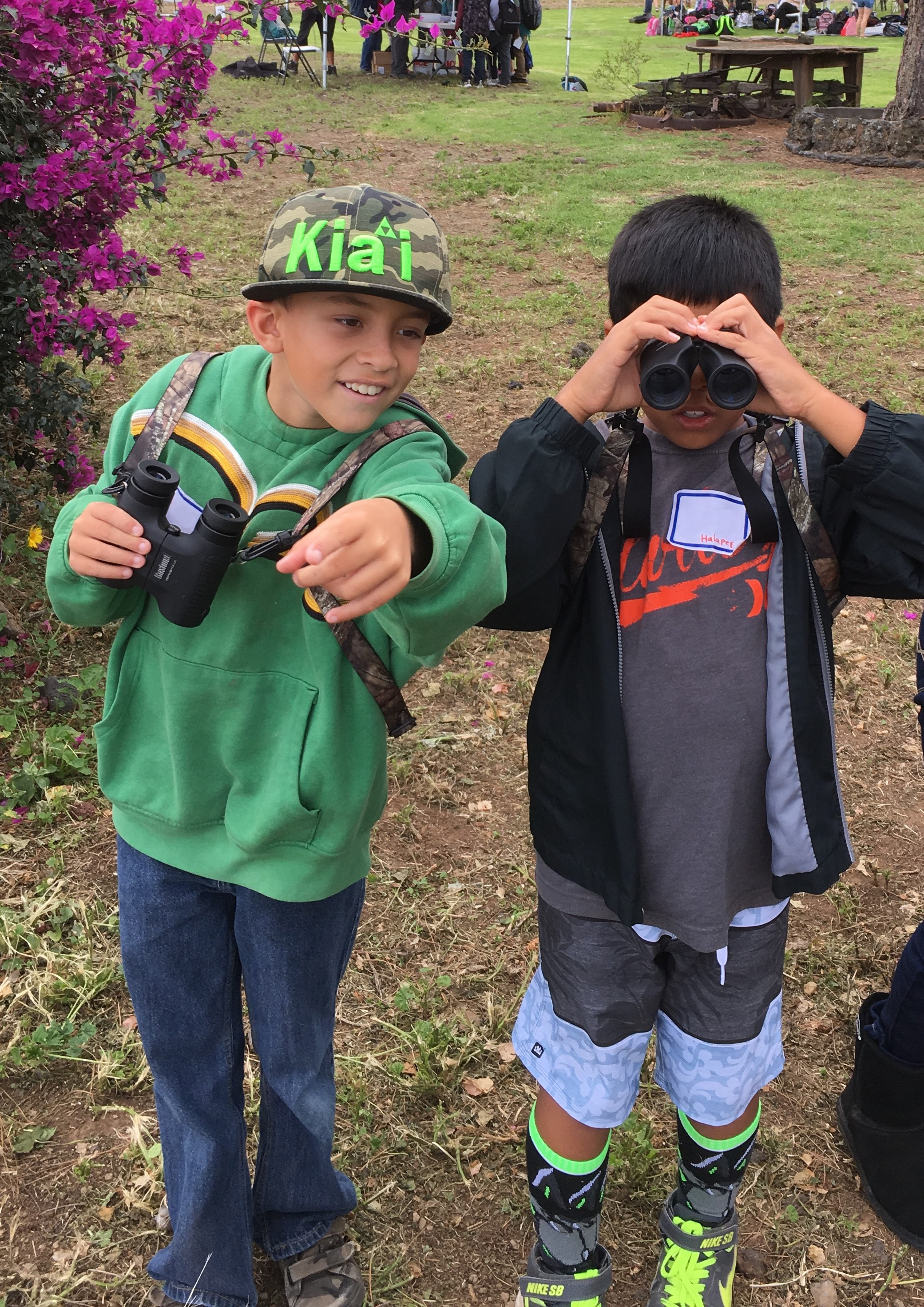 Photo: Tow kids looking through binoculars at native birds (off-camera). One of the kids is pointing at the birds.