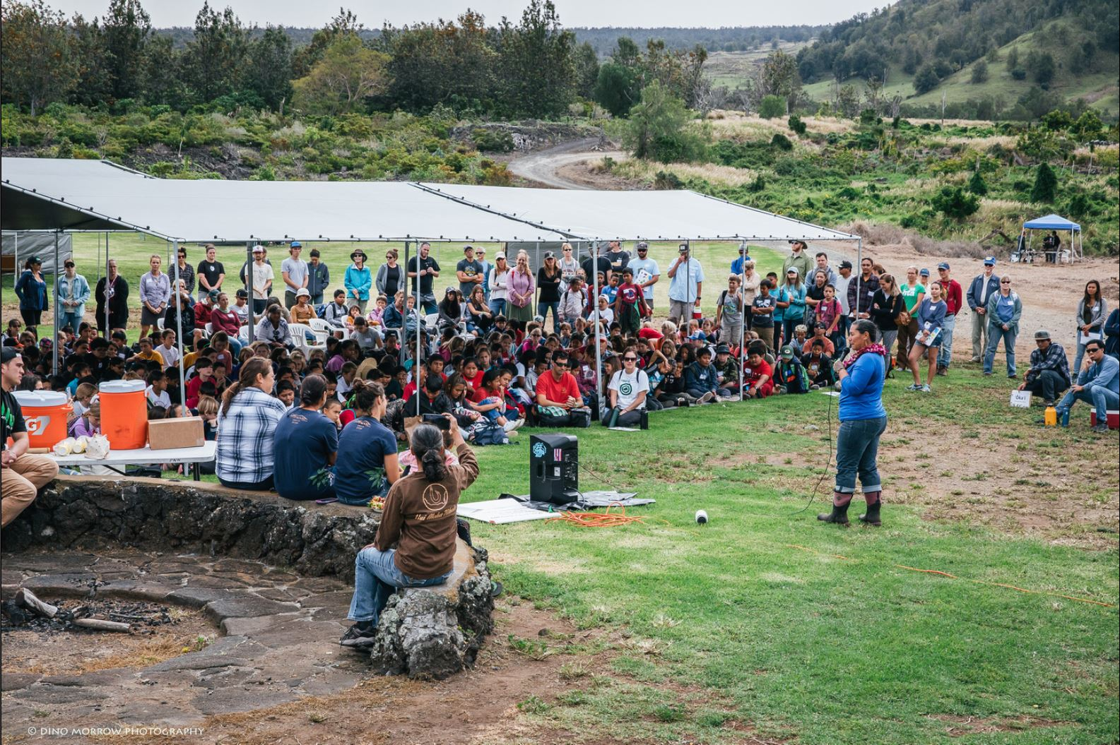 Photo: a group of 250 4th grade students sit calmly under tents as FS personnel innitiate the biocultural blitz.
