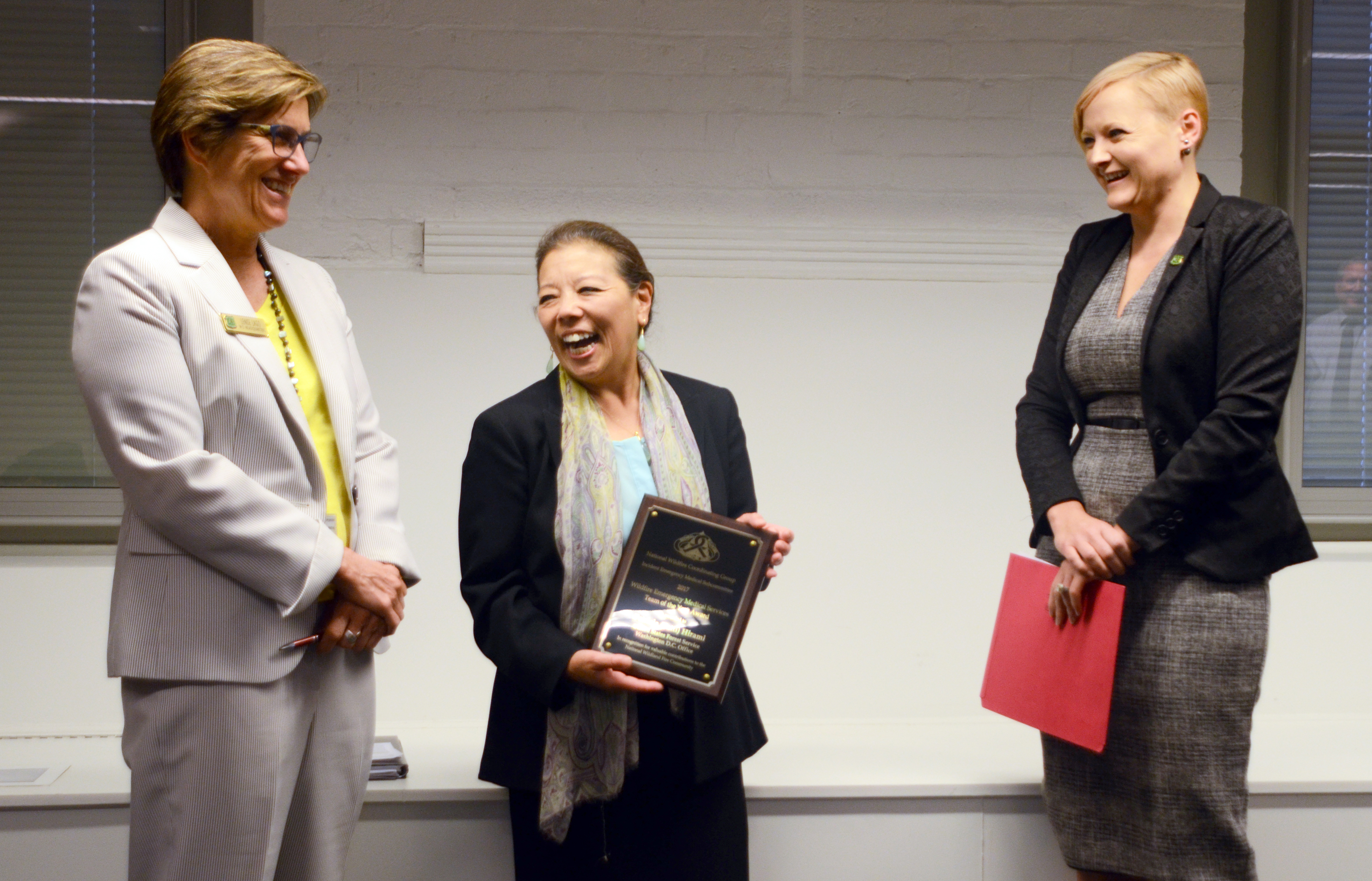 Photo: Lenise Lago, Patti Hirami (holding plaque) and Jaelith Hall-Rivera stand at the front of a room.