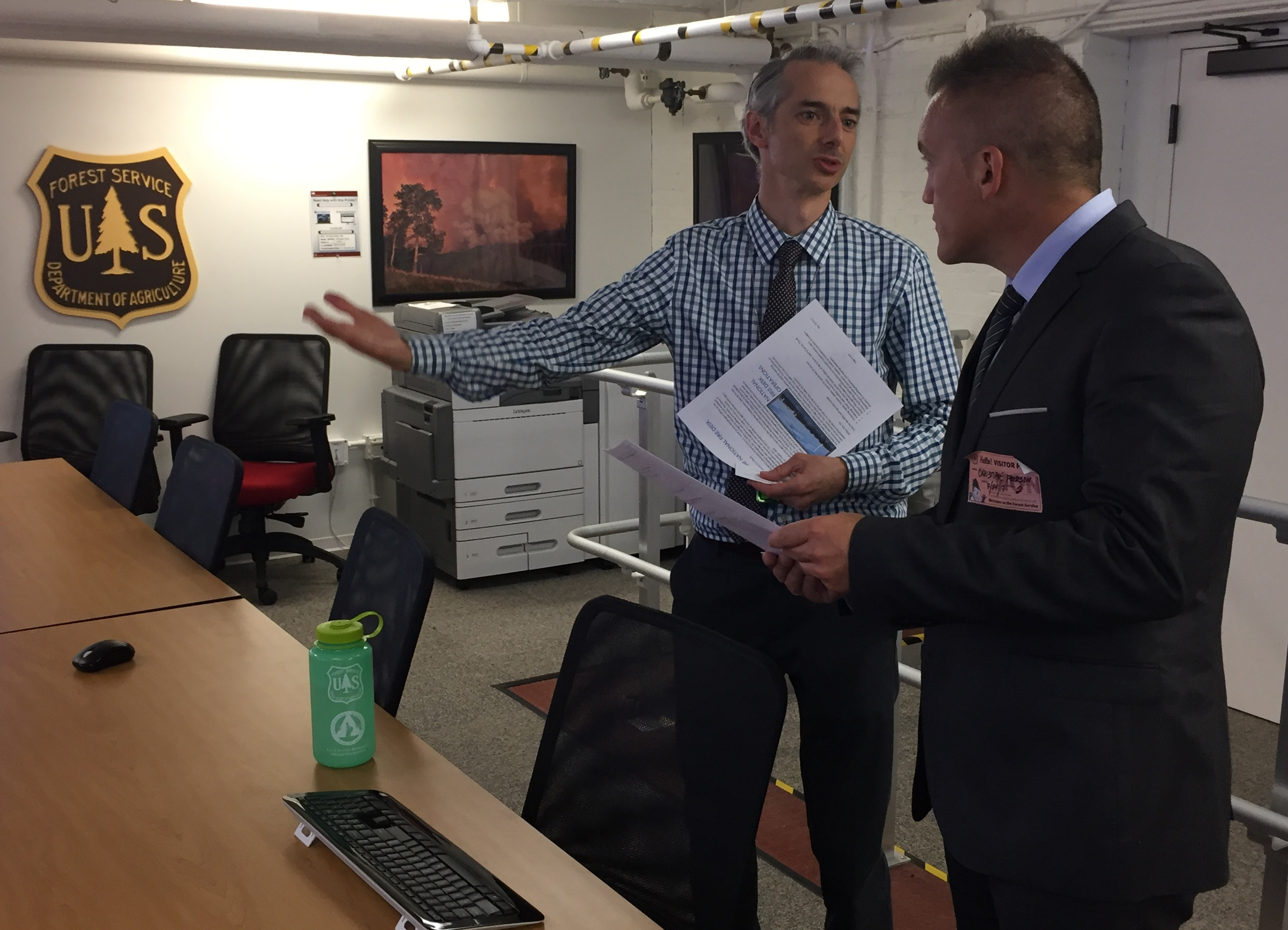 Two individuals having a discussion related to incident management.  Both have papers in hand.