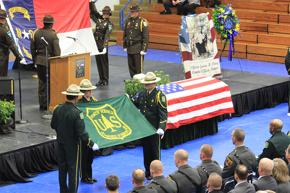 A photo of Honor Guard members begin to fold the U.S. Forest Service and North Carolina State flags